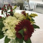 red gerbera daisy centerpiece with hydrangea in clear vase